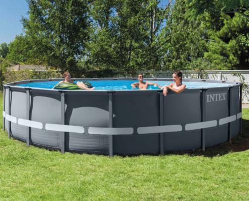 Piscina intex redonda con tres personas ella en una colchoneta flotando y el también la piscinas situada en un jardín